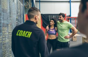 Couple with their coach in the gym