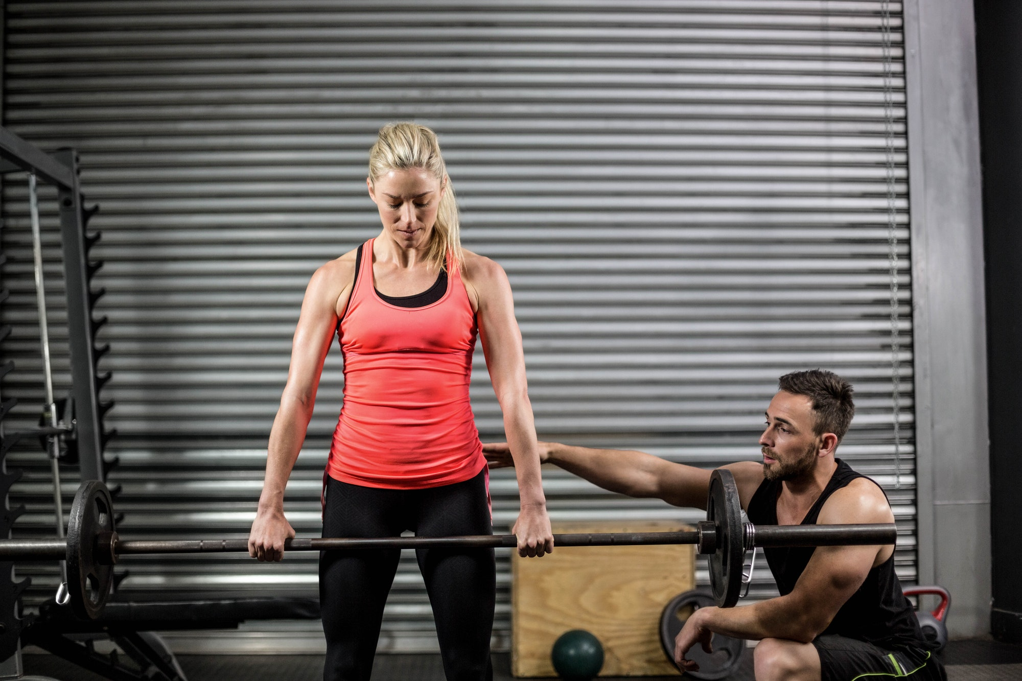 Trainer helping woman with lifting barbell at crossfit gym