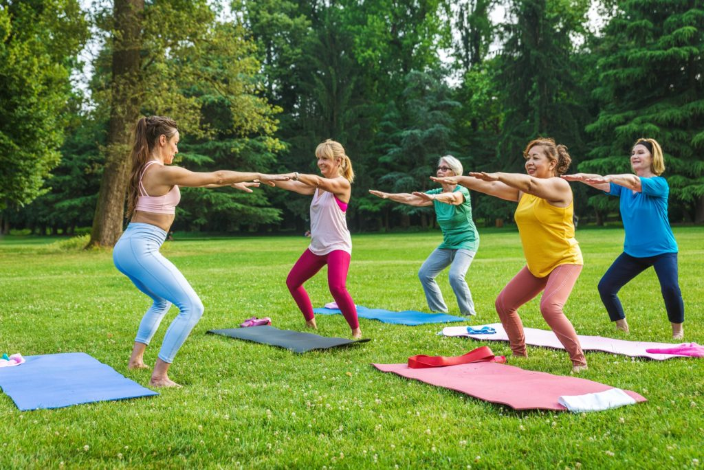 Senior women training with fitness coach at park